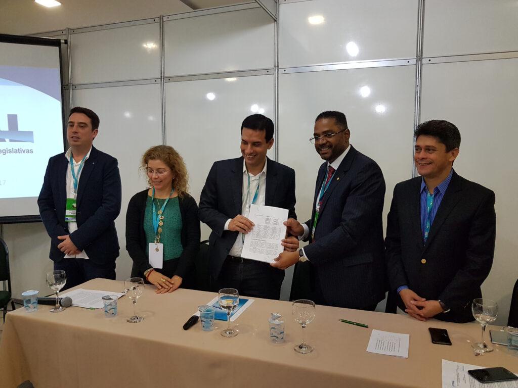 Secretário Márcio Marinho e presidente da Câmara Municipal de Salvador, Leo Prates, mostram termo de cooperação para instalação da Rádio Câmara na capital baiana